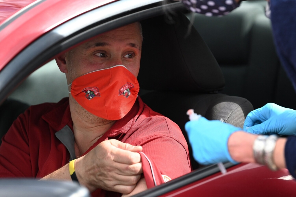 Kyle LeBeau of New Castle lists his shirt to receive a vaccine during a small-scale drive-thru vaccination clinic at Wiscasset Family Medicine onThursday, April 8.
