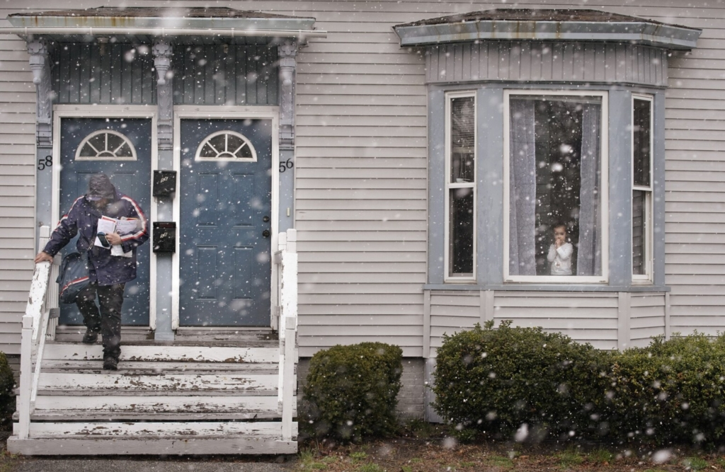 As sleet and snow fall, a girl looks out from a window as Matt Gauthier, a city carrier with the U.S. Postal Service, walks down stairs after delivering mail to a house on Graham Street in Biddeford on Friday.