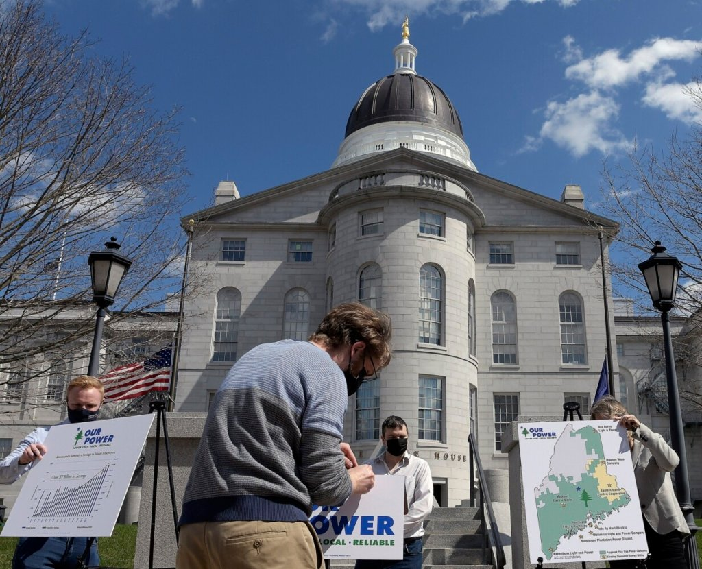 Staffers with Our Power remove signs in Augusta after a news conference on Monday about legislation to create a consumer-owned nonprofit power utility in Maine that would be overseen by an elected board.