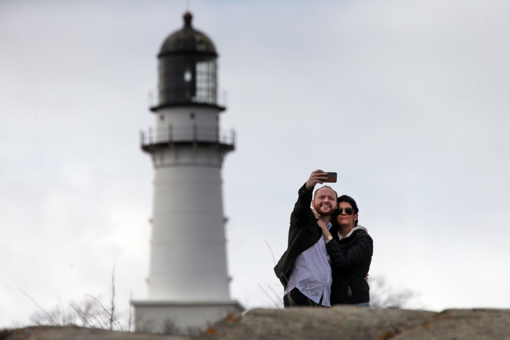 Dylan McKay and Vanessa Cremeans of Salt Lake City, Utah, take a selfie from Dyer Point with Cape Elizabeth Light in the background on April 17. Leaders of Maine's tourism industry are looking forward to the lifting of some travel restrictions on Saturday.