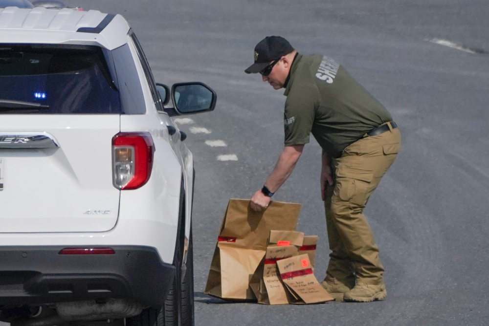 A sheriff's deputy from Frederick County, Md., puts paper bags with evidence into a police vehicle near the scene of a shooting at a business park in Frederick, Md., Tuesday, April 6.