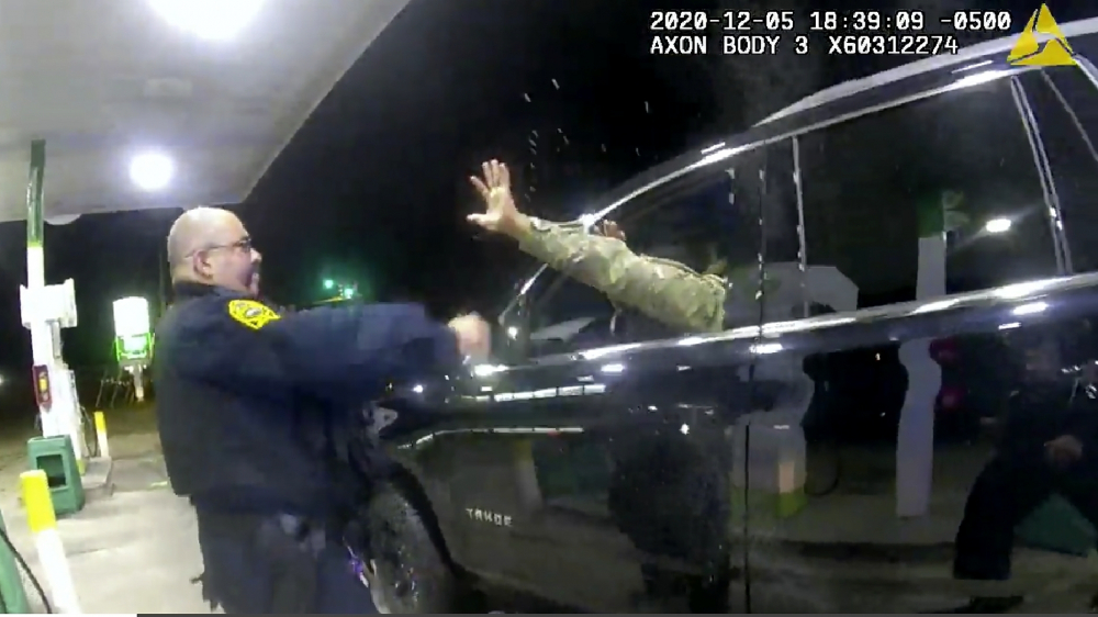 A police officer uses pepper spray on Caron Nazario on Dec. 20, 2020, in Windsor, Va.  Nazario, a second lieutenant in the U.S. Army, is suing two Virginia police officers over a traffic stop during which he says the officers drew their guns and pointed them at him as he was dressed in uniform.