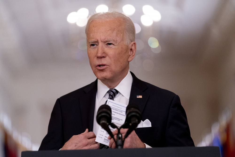 """President Biden holds up a card with his daily schedule and the daily deaths from COVID-19 on March 11 during a primetime address from the East Room of the White House. """"He ran as the antithesis of Trump,"""" said former Barack Obama adviser David Axelrod. """"Empathetic, decent and experienced, and he is delivering."""""""