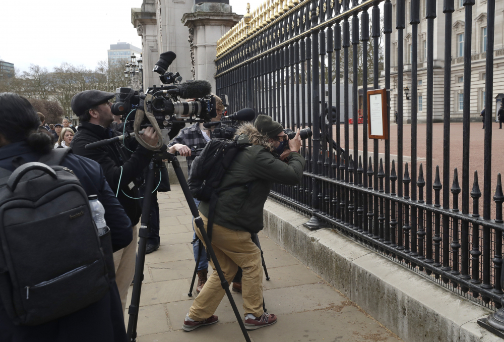 Members of the media take images of an announcement about the death of Britain's Prince Philip displayed on the fence of Buckingham Palace on Friday in London.