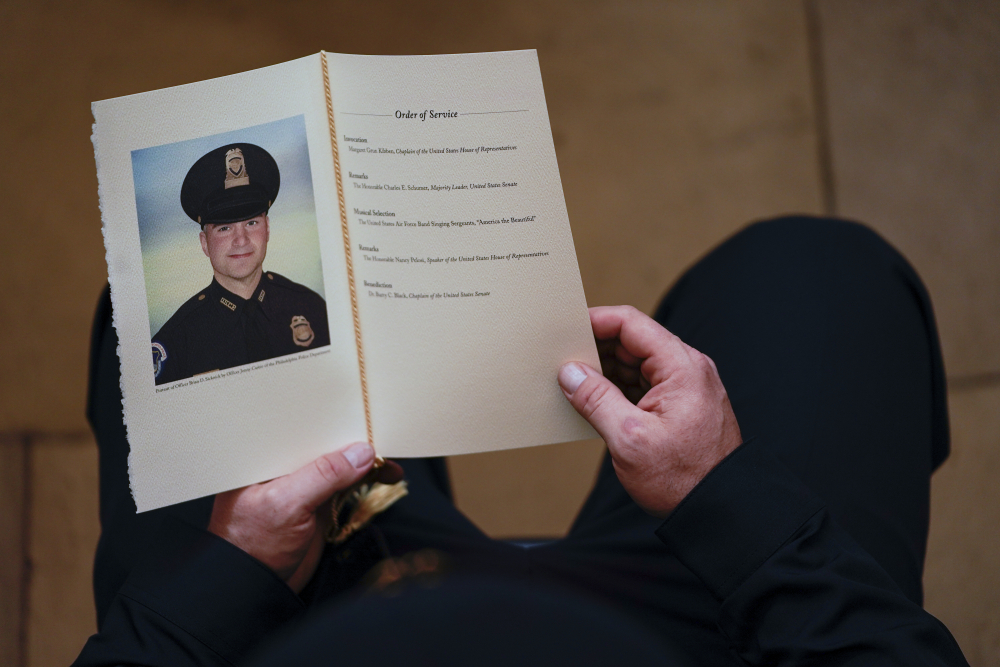 A U.S. Capitol Police officer holds a program during a ceremony memorializing U.S. Capitol Police officer Brian Sicknick on Feb. 3 at the Capitol Rotunda. The medical examiner's findings will likely inhibit the ability of federal prosecutors to bring homicide charges in Sicknick's death.