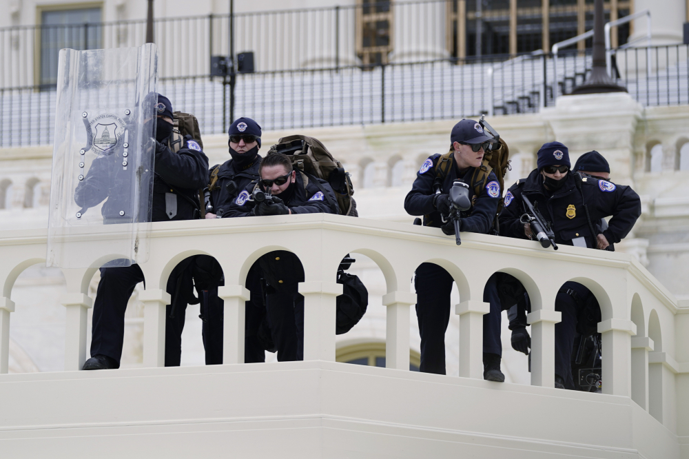 Police keep a watch on demonstrators before they broke through a police barrier at the Capitol in Washington on Jan. 6. A blistering internal report by the U.S. Capitol Police describes a multitude of missteps that left the force unprepared for the insurrection that day.