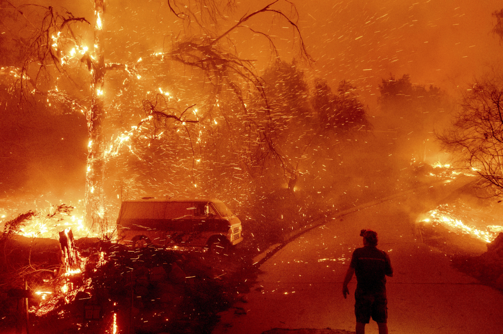 Bruce McDougal watches Dec. 3 as embers fly over his property as the Bond Fire burns through the Silverado community in Orange County, Calif. A