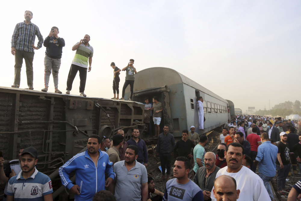 People gather at the site where a passenger train derailed injuring at least 100 people on Sunday in Banha, Egypt.