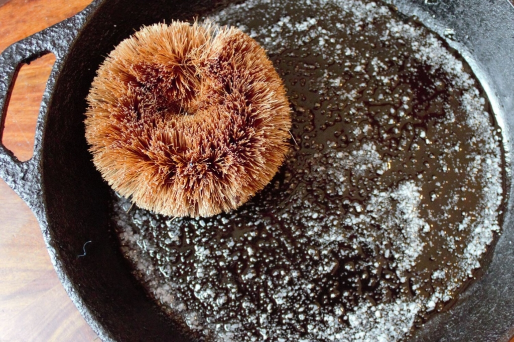 A coconut scouring pad with oil and salt tackles an 8-inch cast iron pan.