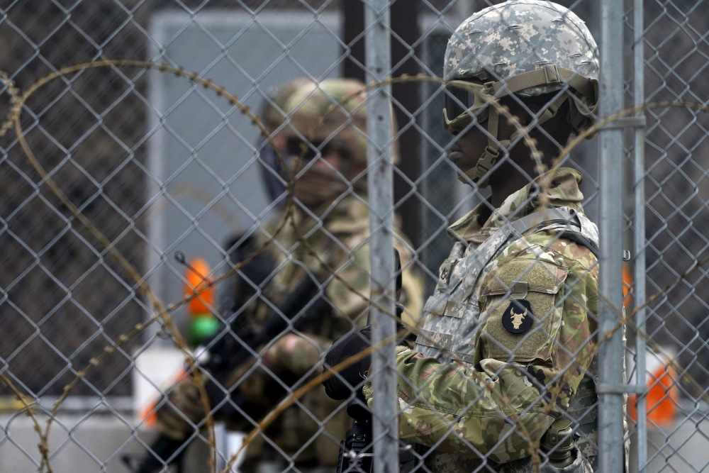 National Guard members are seen through fencing and wire near the Minneapolis Police 3rd Precinct in Minneapolis on Monday, after the murder trial against former Minneapolis police Officer Derek Chauvin advanced to jury deliberations.