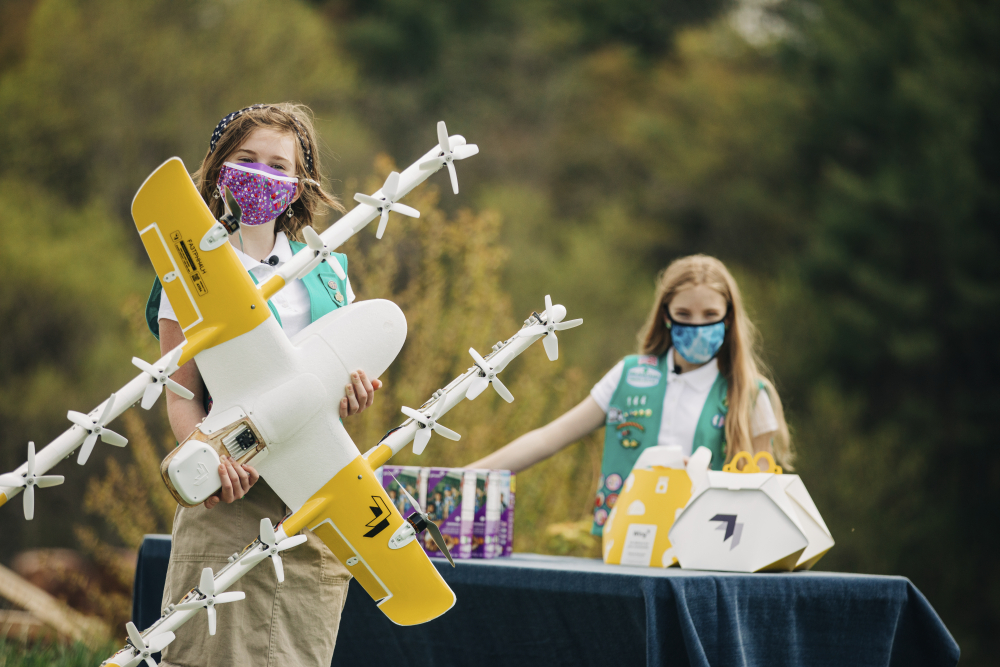 Girl Scouts Alice, right, and Gracie pose April 14 with a Wing delivery drone in Christiansburg, Va.