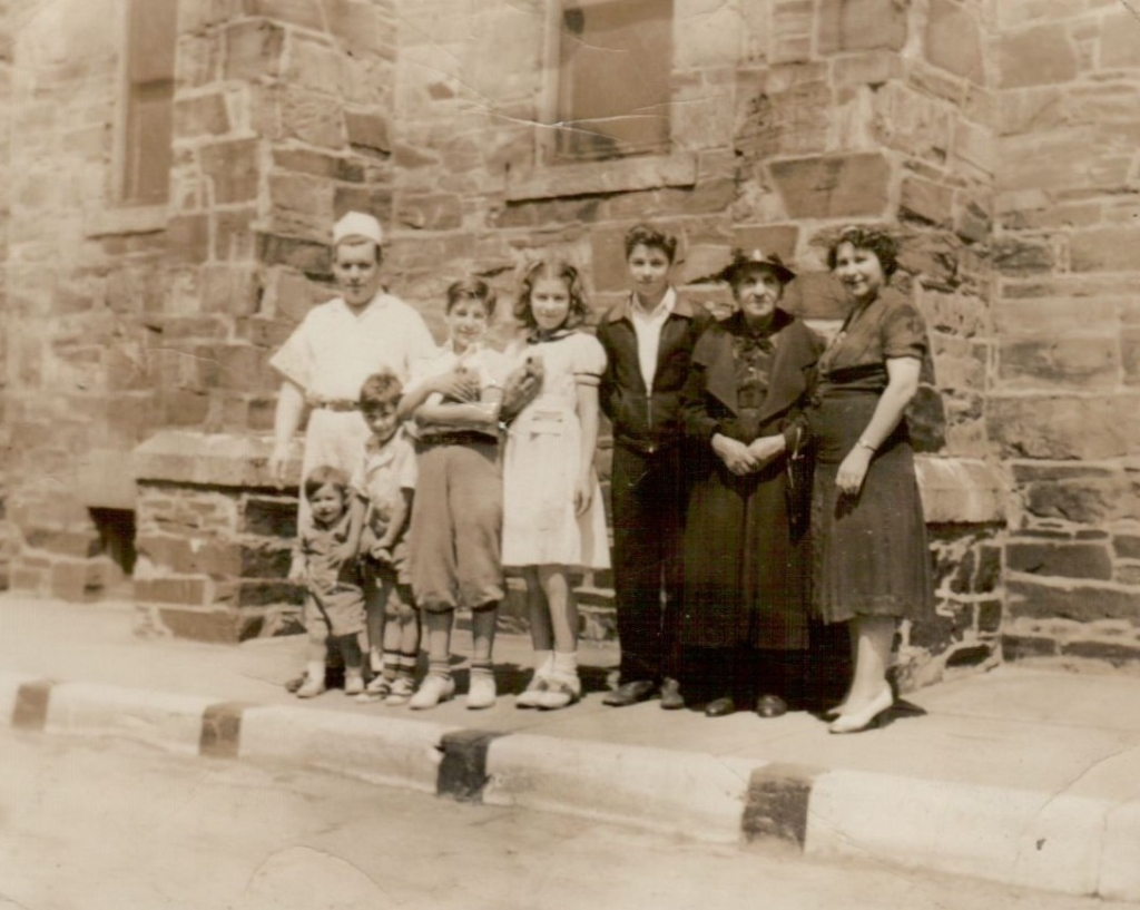The Panagakos family stand in front of Saint Stephen's Church at 667 Congress Street (now luxury hi-rise Hiawatha House) in Longfellow Square.