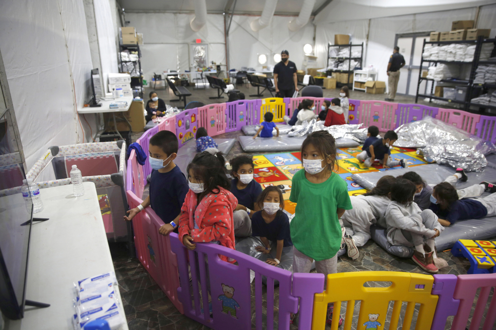 Young unaccompanied migrants, from ages 3 to 9, watch television inside a playpen March 30 at the U.S. Customs and Border Protection facility, the main detention center for unaccompanied children in the Rio Grande Valley, in Donna, Texas.