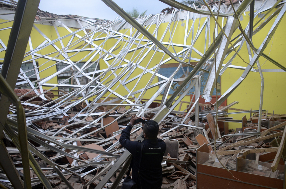 A local journalist films the damage to a classroom at a school after an earthquake in Malang, East Java, Indonesia, on Saturday