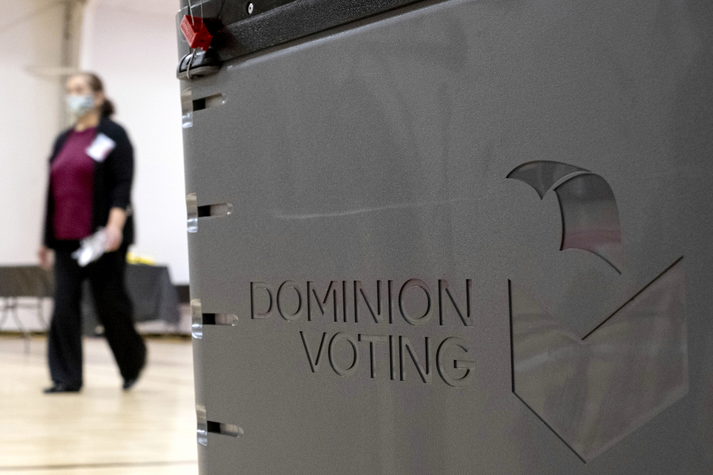 A worker passes a Dominion Voting ballot scanner while setting up a polling location at an elementary school in Gwinnett County, Ga., outside of Atlanta, in January. Newsmax has apologized to an employee of Dominion Voting Systems for airing false allegations that he manipulating voting machines or tallies on Election Day to the detriment of former President  Trump.