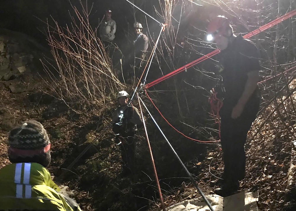 In this photo provided by first responders, rescue crews from Vermont and New Hampshire use a series of ropes and pulleys while working to rescue a man from an abandoned copper mine, late Saturday, in Corinth, Vermont. (Courtesy Hanover Fire Department via AP)