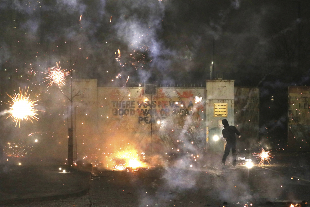 A firework explodes Wednesday as Nationalist and Loyalist rioters clash on Lanark Way in West Belfast, Northern Ireland.