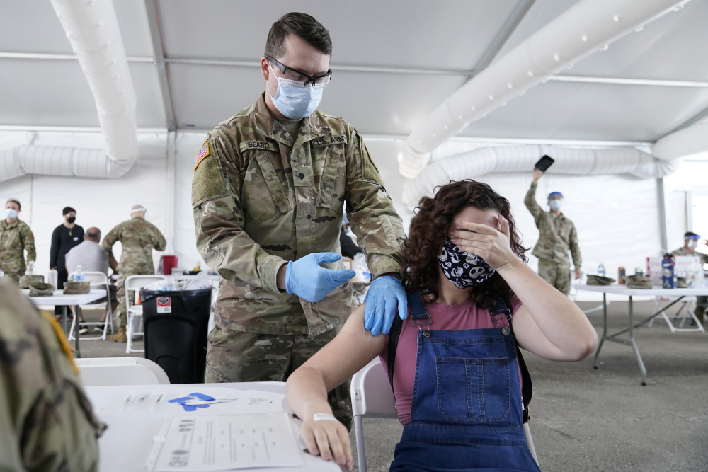 Leanne Montenegro, 21, covers her eyes because she doesn't like the sight of needles, while she receives the Pfizer COVID-19 vaccine at a FEMA vaccination center at Miami Dade College this month in Miami. FEMA has repeatedly reached out to other federal agencies for volunteers to help with the mass vaccination centers.