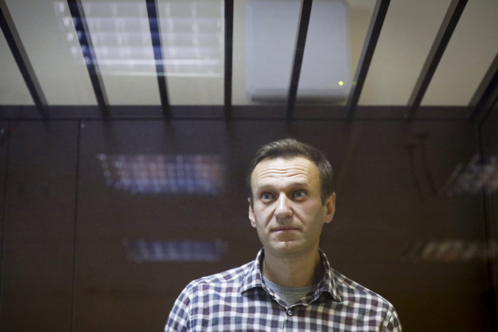Russian opposition leader Alexei Navalny stands in a cage in the Babuskinsky District Court in Moscow, Russia on Feb. 20, 2021.  Navalny, who is in the third week of a hunger strike, will be admitted to a hospital in another prison, the Russian state penitentiary service said Monday.