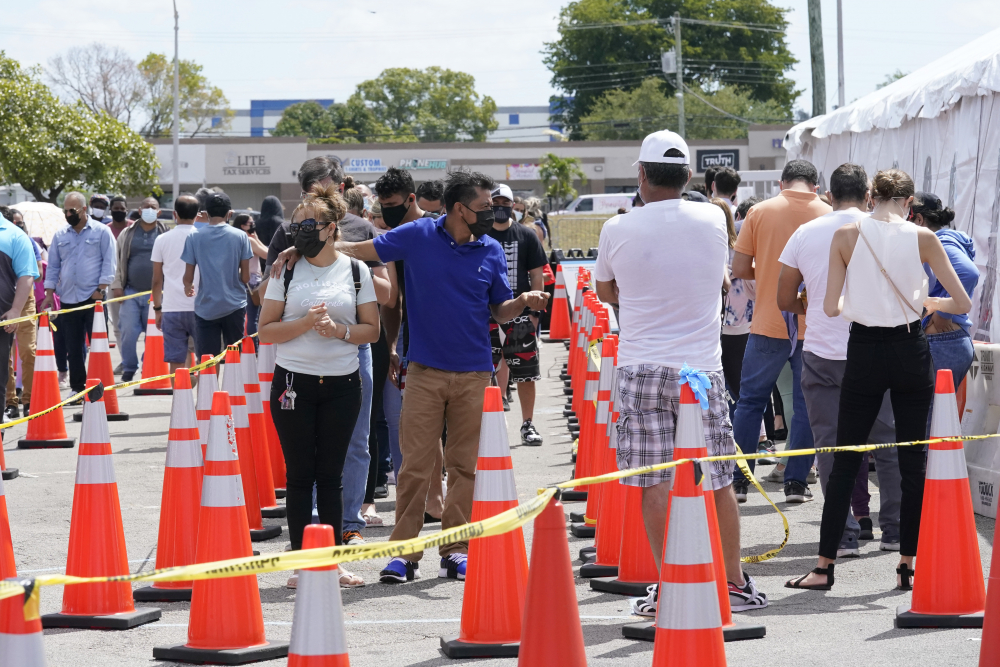 People wait in line to receive a COVID-19 vaccine at a FEMA vaccination center at Miami Dade College last month in Miami.