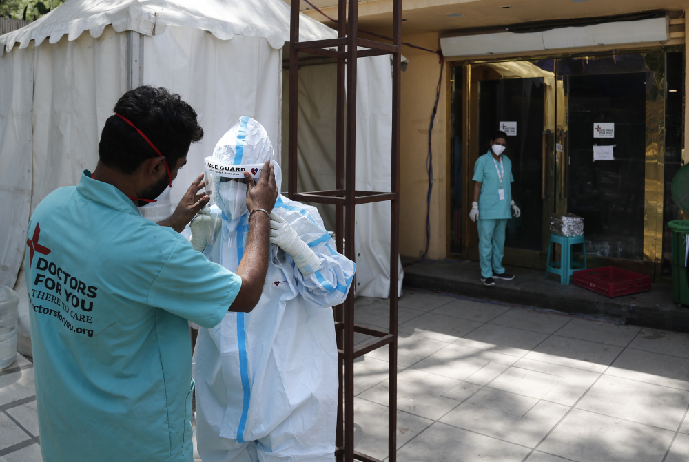 A health worker adjusts the face shield of another as she prepares to go inside a quarantine center for COVID-19 patients in New Delhi, India on April 19.