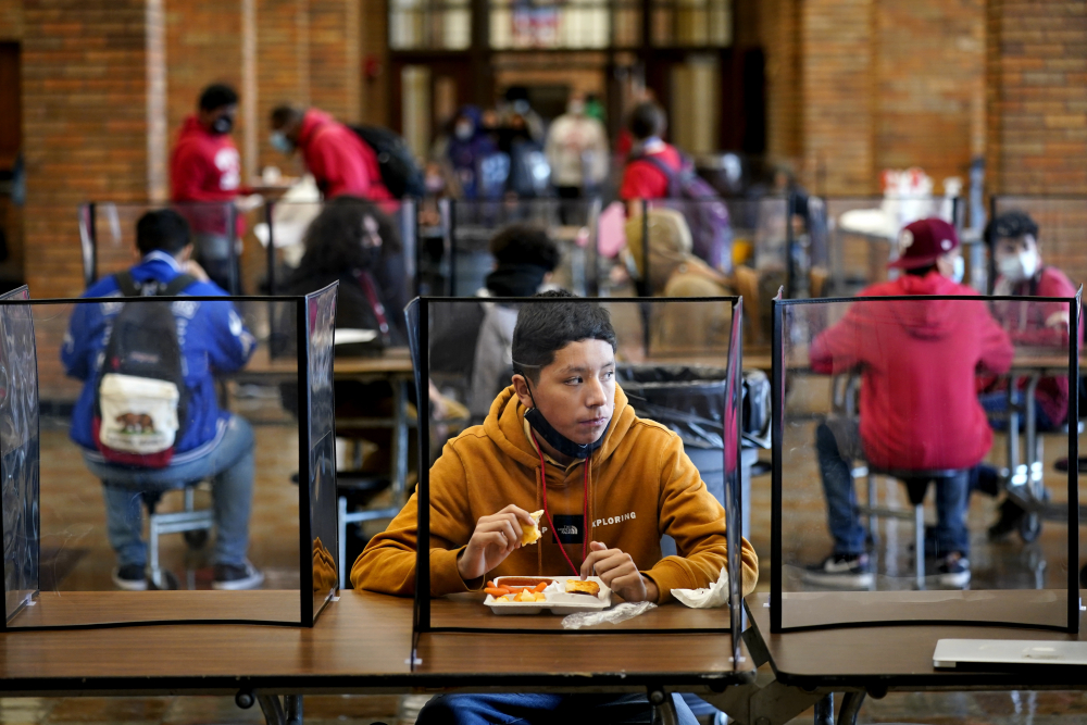 Freshman Hugo Bautista eats lunch at Wyandotte County High School on Wednesday in Kansas City, Kan., on the first day of in-person learning.