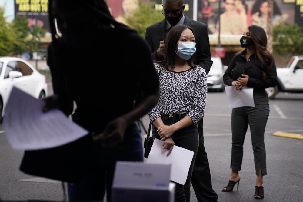People wait in line, resumes in hand, while waiting to apply for jobs during an outdoor hiring event for the Circa resort and casino, Tuesday in Las Vegas.