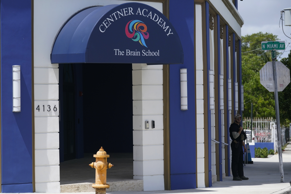 A security guard walks the perimeter of the Centner Academy this month in Miami. The private school founded by an anti-vaccination activist in South Florida has warned teachers and staff against taking the COVID-19 vaccine.