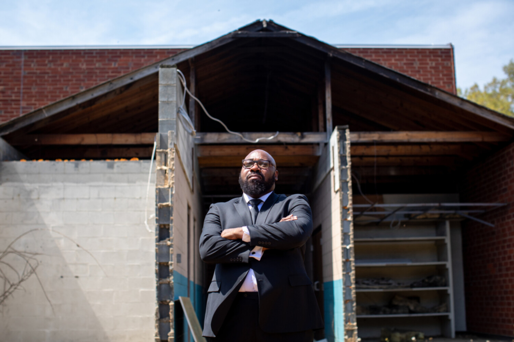 Pastor Kenneth Robinson stands in front of a section of Briar Creek Road Baptist Church in Charlotte, N.C., that was set on fire in 2015.