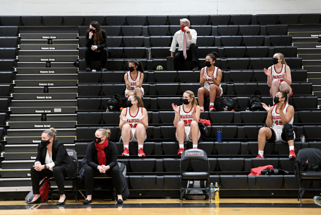 James Madison High School basketball players cheer from the bench during the second half against Osbourn Park on Feb. 20 in Vienna, Va.