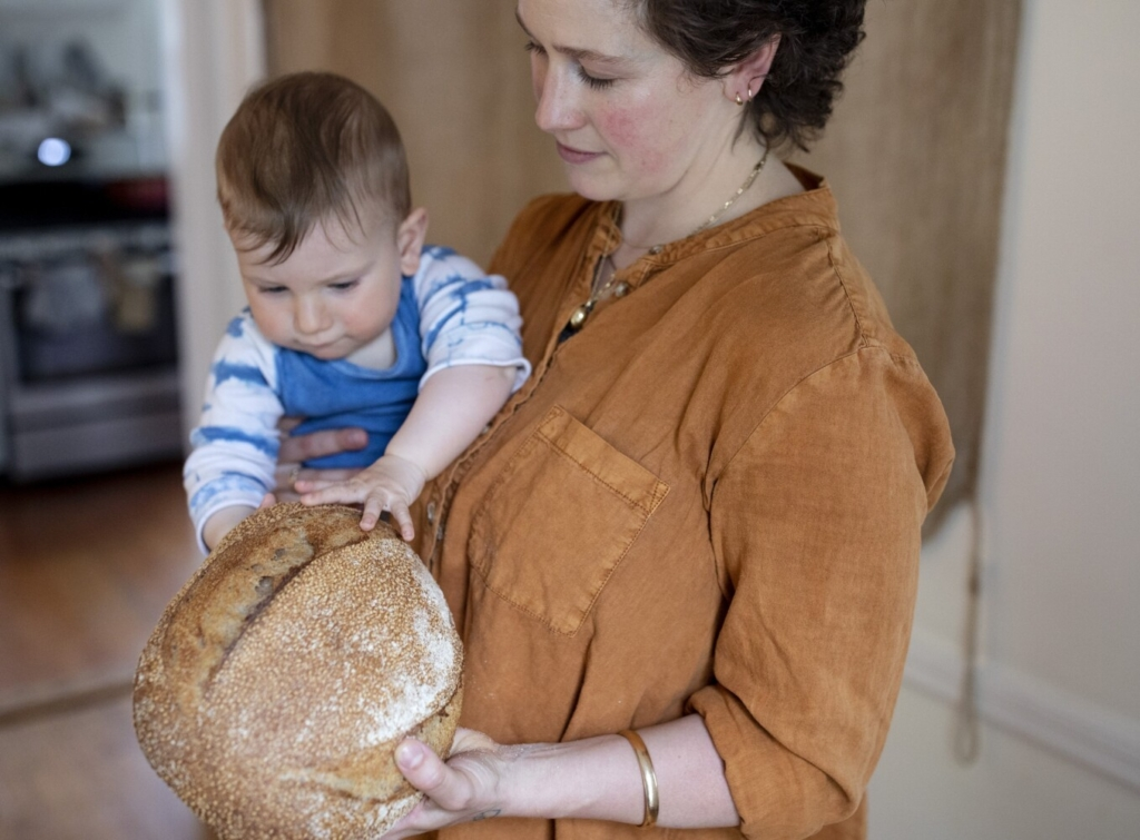 Ten-month-old Sandy Winthrop inspects a loaf of his mom Kate Whittemore's homemade tahini-wheat sourdough a few days before Mother's Day.  Whittemore gave some of her same sourdough starter to Rose Foods owner Chad Conley, where it's used to make the bagels.