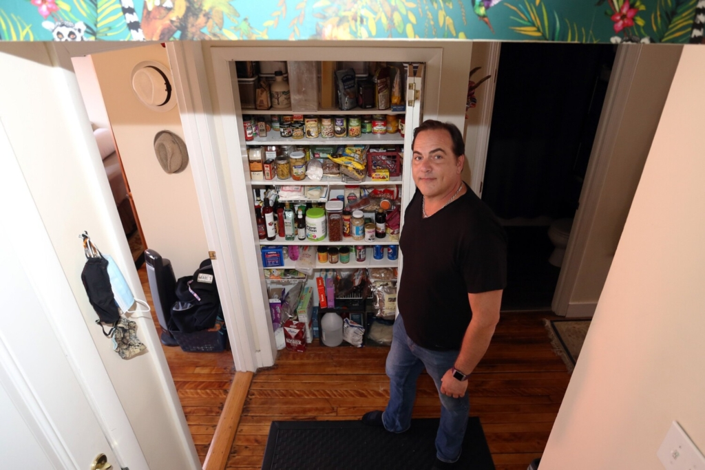 Eric Flynn, owner of Excellence Realty, displays the many pantry staples he squirreled away during the pandemic. He installed new shelves in the hallway so he would have a place to store the food. As you can see, the shelves are still very well-stocked.