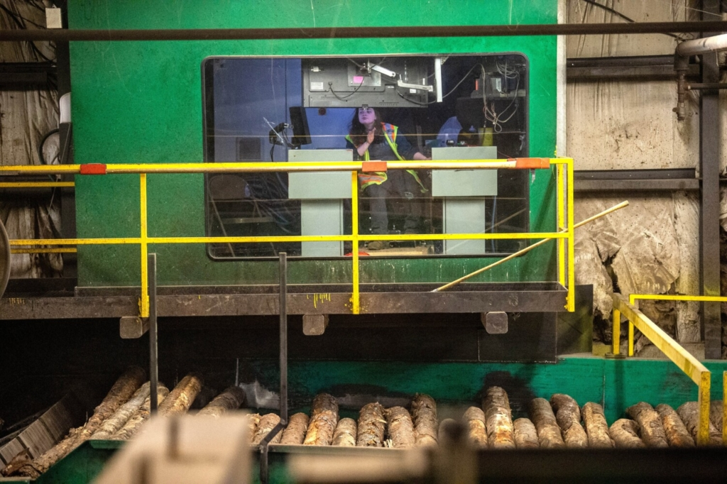 Keri Libby sits in the operator's cockpit of the de-barker machine at Moose River Lumber in Jackman on May 10.