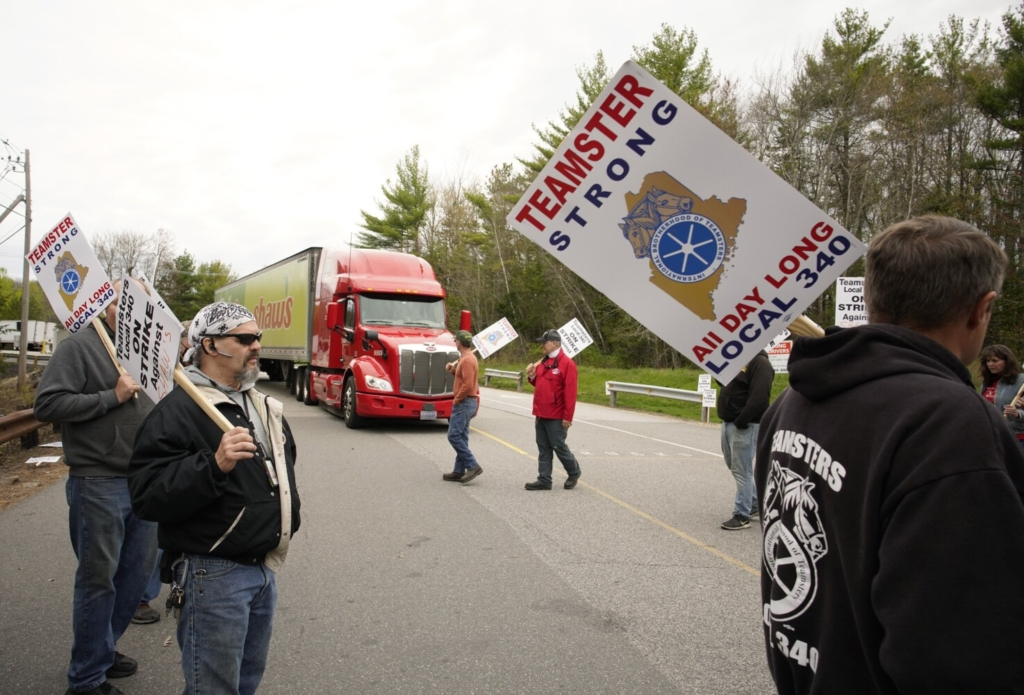 Randy Willis, left, and other drivers with Shaw's supermarkets walk a picket line as a truck leaves the Shaw's distribution facility in Wells on Monday.