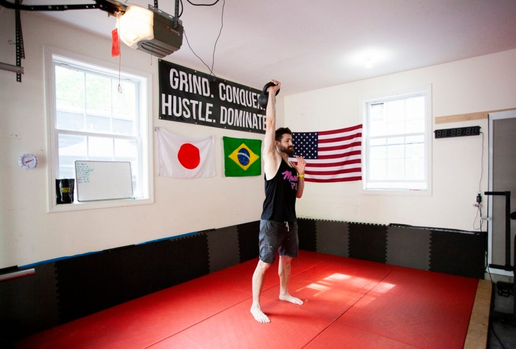 Austin Miller, chef and owner of Mami, works out with a kettlebell in his home gym on a recent May day. Miller built a home gym in his garage during the pandemic to alleviate stress and says he is in the best shape of his life now.