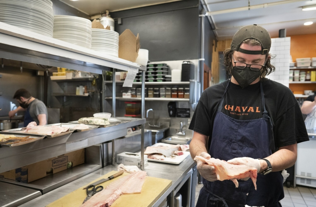 Kirby Sholl, chef de cuisine at Chaval, shows a section of halibut ribs. For the restaurant's Halibut Project, he's developed  a number of recipes that use off-cuts like the ribs, to entice customers to eat more than the usual fillets and, not incidentally, to waste less of the fish.