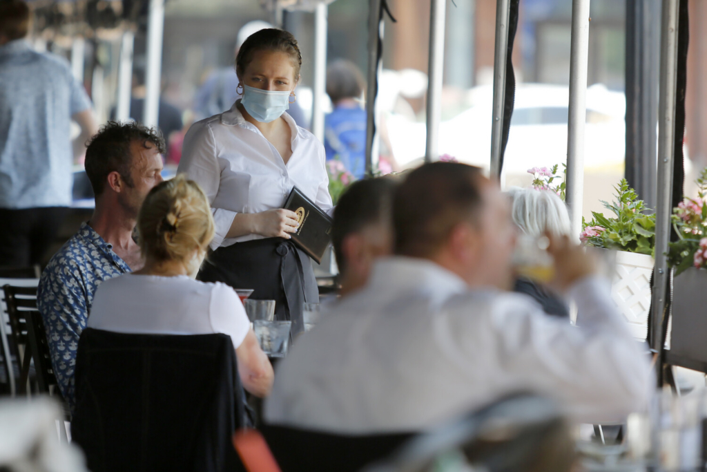 A server prepares to take an order from customers seated outside at Legal Sea Foods on Wednesday in Boston.