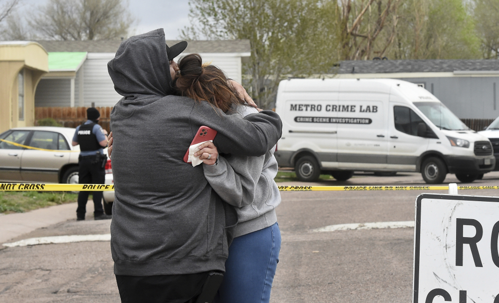 Freddy Marquez kisses the head of his wife, Nubia Marquez, near the scene where her mother and other family members were killed in a mass shooting early Sunday in Colorado Springs, Colo.