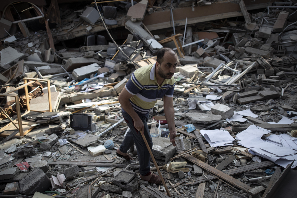 A Palestinian man inspects the damage of a house destroyed by an early morning Israeli airstrike, in Gaza City, Tuesday, May 18. Israel carried out a wave of airstrikes on what it said were militant targets in Gaza, leveling a six-story building in downtown Gaza City, and Palestinian militants fired dozens of rockets into Israel early Tuesday, the latest in the fourth war between the two sides, now in its second week.