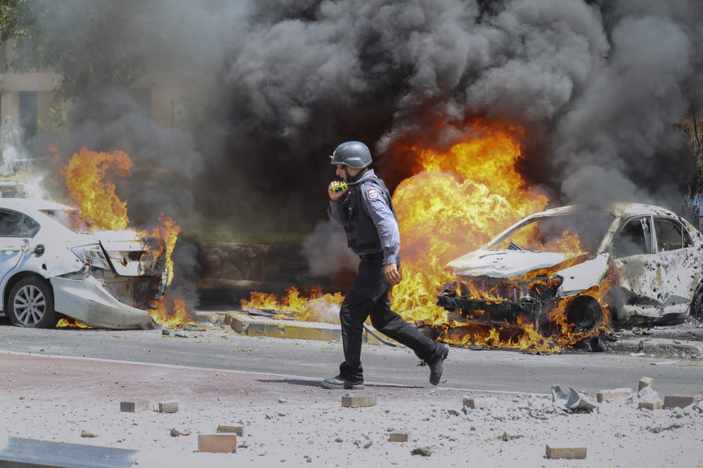 An Israeli firefighter walks next to cars hit by a missile fired from Gaza Strip, in the southern Israeli town of Ashkelon, Tuesday, May 11.