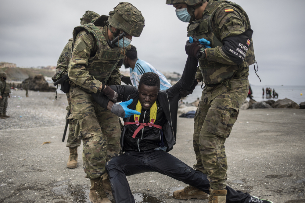 A man is held by soldiers of the Spanish Army at the border of Morocco and Spain, at the Spanish enclave of Ceuta, on Tuesday. Around 6,000 people had crossed by Tuesday morning since the first arrivals began in the early hours of Monday, including 1,500 who are presumed to be teens.