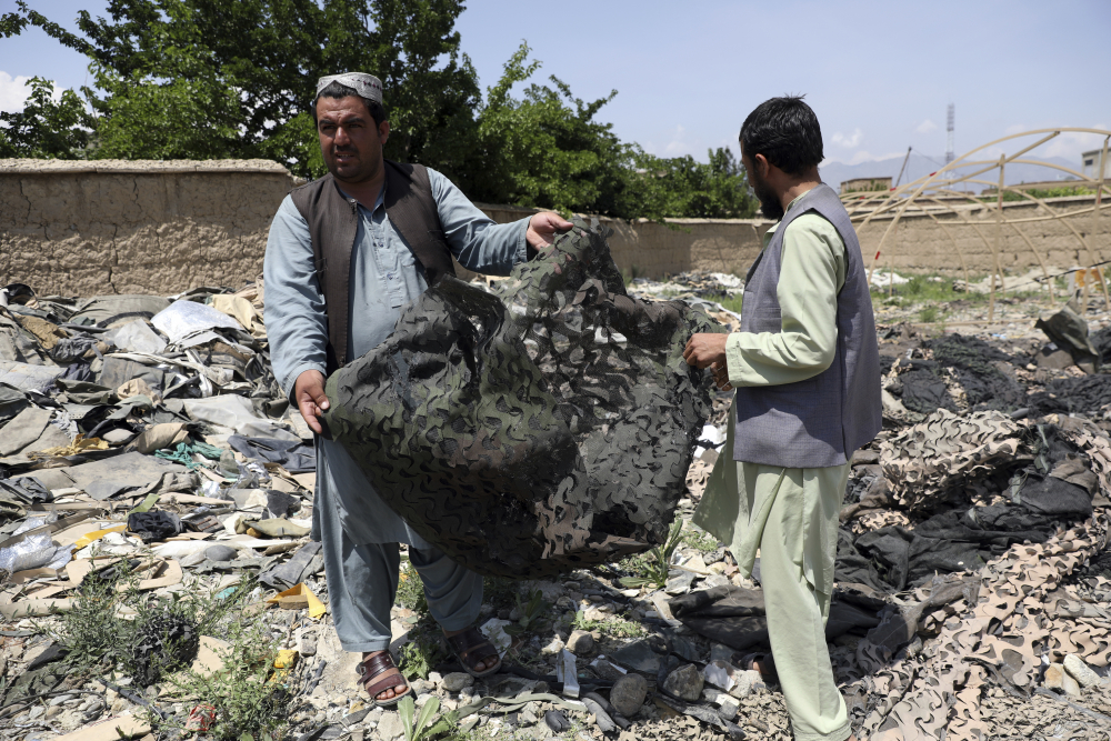 Afghan men hold scraps of tenting at a scrapyard outside Bagram Air Base, northwest of Kabul, Afghanistan, on Monday.
