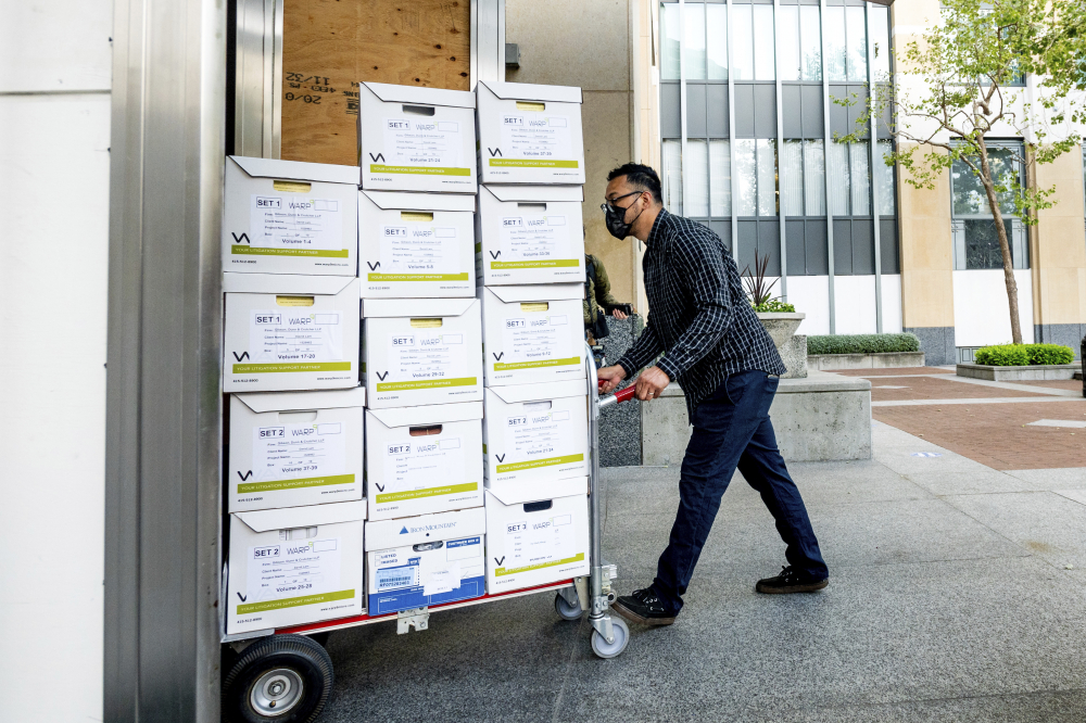 A member of Apple's legal team rolls exhibit boxes into the Ronald V. Dellums building in Oakland, Calif., as the company faces off in federal court against Epic Games on Monday. Epic, maker of the video game Fortnite, charges that Apple has transformed its App Store into an illegal monopoly.