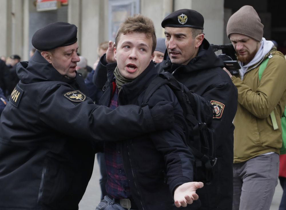 Belarus police detain journalist Raman Pratasevich, center, in Minsk, Belarus in March 2017. Pratasevich, a founder of a messaging app channel that has been a key information conduit for opponents of Belarus' authoritarian president, has been arrested after an airliner in which he was riding was diverted to Belarus because of a bomb threat. The presidential press service said President Alexander Lukashenko personally ordered that a MiG-29 fighter jet accompany the Ryanair plane — traveling from Athens, Greece, to Vilnius, Lithuania — to the Minsk airport.