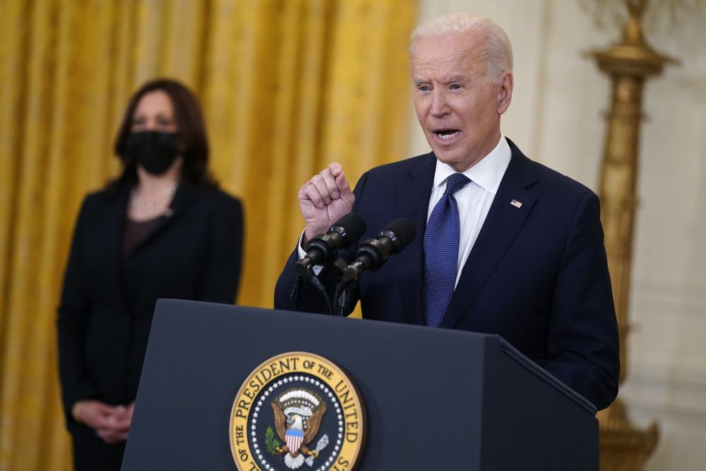 """Vice President Kamala Harris listens as President Biden speaks about the economy on Monday in the East Room. """"We're moving in the right direction,"""" Biden said. """"I never said ... that climbing out of the deep, deep hole our economy was in would be simple, easy, immediate or perfectly steady."""