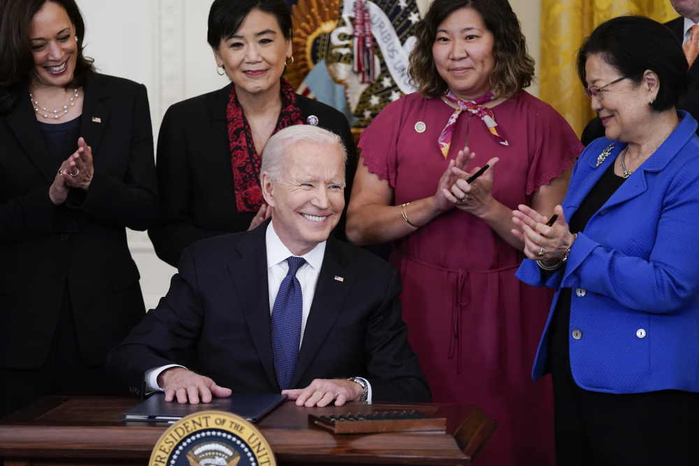 President Biden smiles after signing the COVID-19 Hate Crimes Act, in the East Room of the White House on Thursday in Washington. Top row from left, Vice President Kamala Harris, Rep. Judy Chu, D-Calif., Rep. Grace Meng, D-N.Y., and Sen. Mazie Hirono, D-Hawaii.
