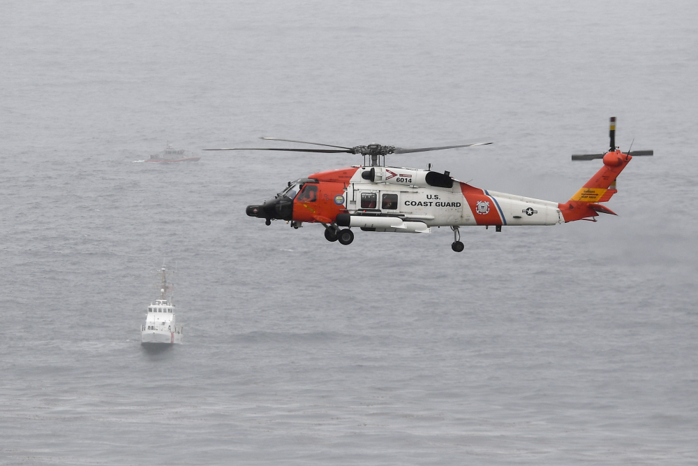 A U.S. Coast Guard helicopter flies over boats searching the area where a boat capsized just off the San Diego coast on Sunday. Authorities believe everyone is accounted for but continued to search.