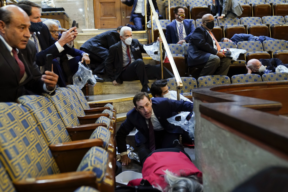 People shelter in the House chamber as rioters try to break in at the U.S. Capitol in Washington during the Jan. 6 insurrection.
