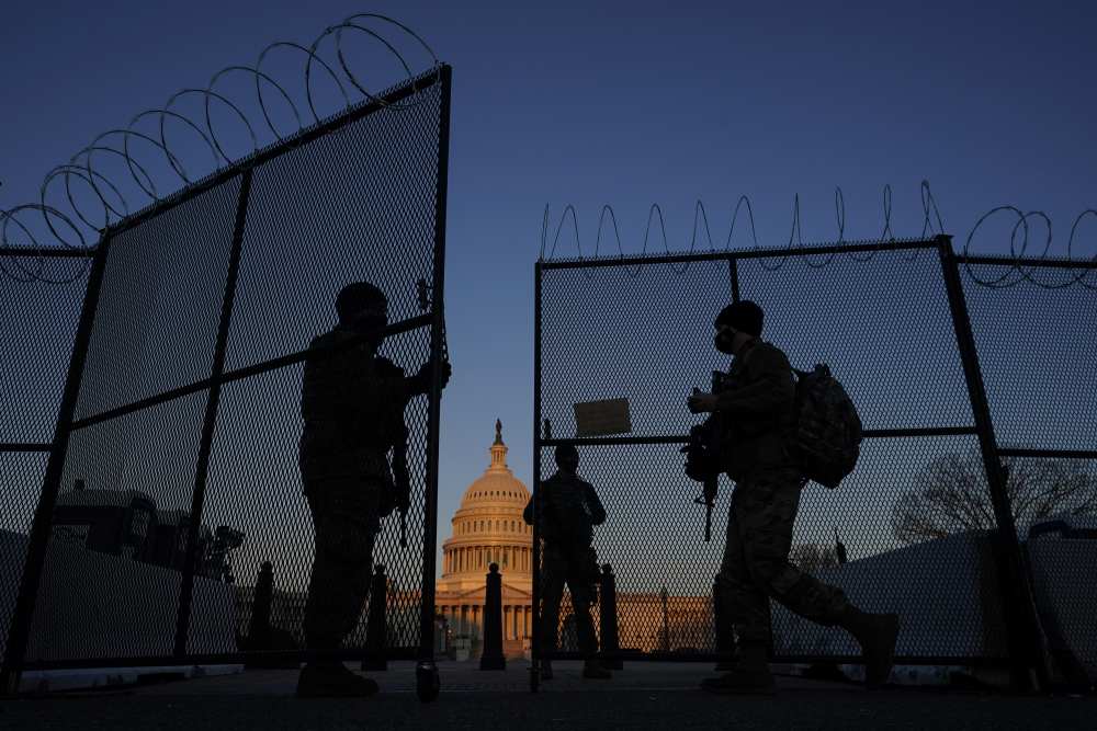 Members of the National Guard open a gate in the razor wire-topped perimeter fence around the U.S. Capitol at sunrise in Washington in March. Threats to members of Congress have more than doubled this year, according to the U.S. Capitol Police.
