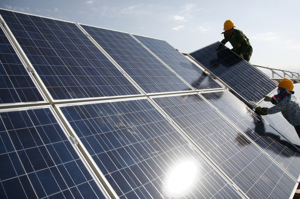 """Workers install solar panels at a photovoltaic power station in Eastern Xinjiang, China. John Kerry, the U.S. climate enjoy, told legislators last week that the administration believes  solar panels """"in some cases are being produced by forced labor."""""""
